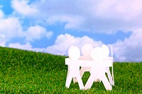 Concept image circle of paper men holding hands in a field with sky background