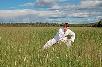 oung man practices Wushu in field