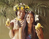 Young couple holding tropical fruits, close_up