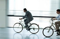 Businessmen riding bicycles indoors, silhouette, blurred motion
