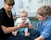 Paediatric nursing. Paediatric nurse and mother in a hospital ward caring for a 5_month_old baby girl who has just undergone dialysis. This is where w...
