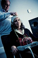 Scientist attaches wires to a female patient aged 18_20 years wearing an electroencephalogram EEG cap that monitors brain activity during an audiology...