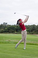 A female golfer swinging her golf club, teeing off