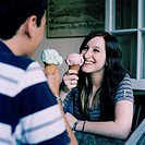 A couple eating ice cream cones, face to face