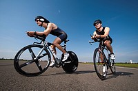 Two cyclists on racing bicycles, side view, low angle view