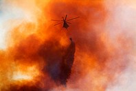 A helicopter drops water on a mountain fire  Table Mountain, Cape Town, South Africa