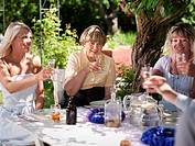 People having drinks in garden, smiling