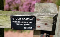 Gate sign asking people to close and fasten the gate because of stock grazing, Peak District National Park, England, UK