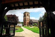 Looking through the Lych Gate towards St Oswald's Church, Lower Peover, Cheshire, England, UK