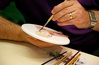 A demonstration of hand painting a china plate at the Wedgwood visitor centre, Barlaston, Stoke-on-Trent, Staffordshire, England