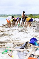 Young people cleaning a tropical beach