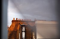 Chimneys on the top of a London's building through the window and curtains
