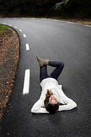 Woman lying on the road, Montseny Natural Park, Barcelona, Catalonia, Spain