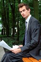 young caucasian businessman in park looking at the documents in his hand