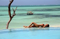 Young woman relaxing in the swimming pool at Pongwe Beach Hotel, Zanzibar, Tanzania