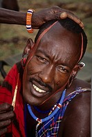 Kenya, Amboseli, Maasai man having ochre applied to his face.