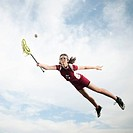 Caucasian teenager in mid_air playing lacrosse