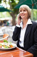 Businesswoman talking on phone at lunch