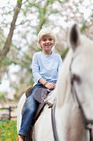 Smiling boy riding horse