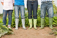 Family wearing rain boots in garden