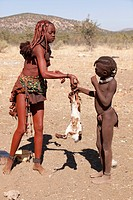 Africa, Namibia, Opuwo. Himba woman and child with baby goat. Credit as: Wendy Kaveney / Jaynes Gallery / DanitaDelimont.com