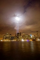 The lights of the downtown New York City skyline reflect off the East River on a cloudy night. The lights from the World Trade Center Memorial create ...