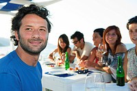 Man smiling at table with friends