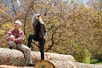 Senior couple with binoculars on tree logs, Italy, Telve, Dolomites