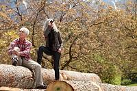 Senior couple with binoculars on tree logs, Italy, Telve, Dolomites