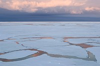 Antarctica, Lazarev sea. Cracks in pack ice. Sunset reflecting in water.