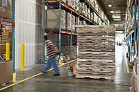 Worker pulling pallets in warehouse