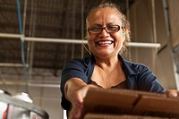 Hispanic woman packing boxes in factory