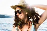 Woman in straw hat smiling on beach