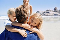 Father hugging children on beach