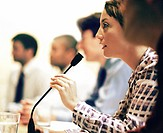 Businesswoman asking question into microphone at meeting