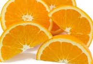 Segments of ripe, juicy oranges piled up, on a white background.