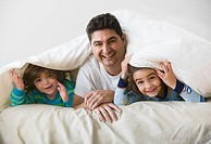 Mixed race father and sons laying under covers in bed