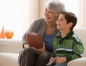 Caucasian grandmother and grandson watching football together