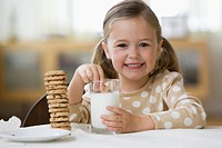 Caucasian girl dunking cookies in milk