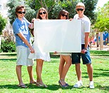 Teens with white billboard standing in park