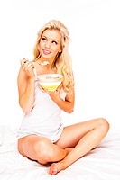 Sexy Woman sitting on bed eating cereal smiling