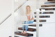 Woman sitting on staircase using laptop