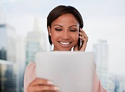 Businesswoman holding digital tablet and talking on cell phone