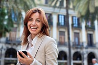 Smiling businesswoman text messaging on cell phone