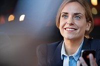 Smiling businesswoman holding cell phone