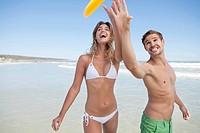 Couple catching plastic disc on beach