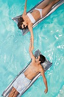 Couple floating in swimming pool holding hands