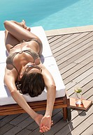 Teenager sunbathing on lounge chair near swimming pool