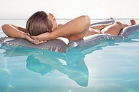 Woman floating in swimming pool sunbathing (thumbnail)