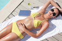 Woman in bikini sunbathing near swimming pool
